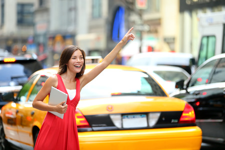 Girl calling taxi cab in New York City, holding tablet pc computer standing in cute summer dress in street of Manhattan, USA  Beautiful young mixed race Asian Caucasian woman outdoor