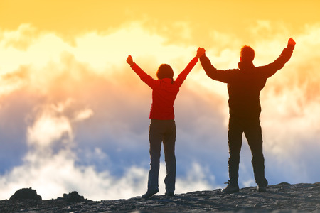 Photo for Happy winners reaching life goal - success people at summit. Business achievement concept. Two person couple together arms up in the air of happiness with accomplishment in the clouds at sunset. - Royalty Free Image