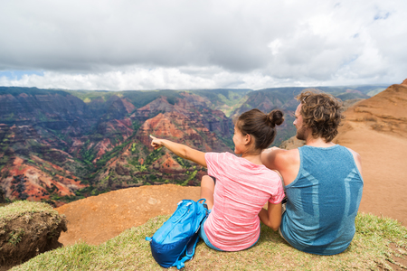 Photo for People hiking in Hawaii hikers pointing at Kauai. happy hiker couple healthy lifestyle outdoors looking at Waimea canyon view. Young couple resting sitting in nature in Kauai, Hawaii, USA. - Royalty Free Image