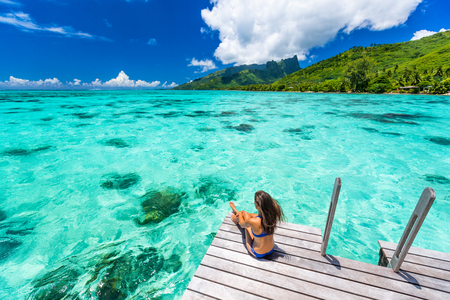 Photo for Bora bora luxury travel overwater bungalow resort vacation bikini woman at Tahiti hotel. Tropical exotic destination. Girl relaxing sitting on private balcony under the sun looking at ocean. - Royalty Free Image