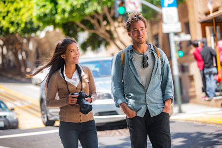 Photo for Young students couple tourists walking in city street taking photos with camera on travel. Asian woman, Caucasian man friends urban lifestyle casual. - Royalty Free Image