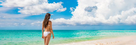 Photo pour Beach vacation travel luxury bikini woman relaxing on summer holidays with copy space ocean, sky horizontal banner panorama landscape background. - image libre de droit