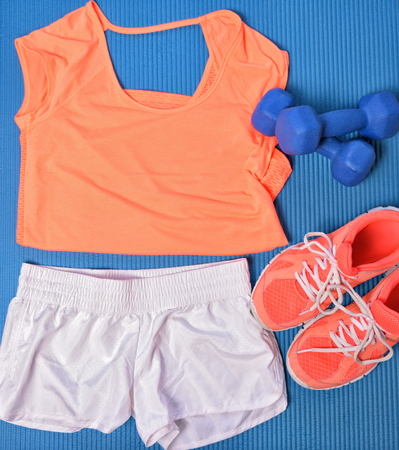 Photo pour Gym clothes for fitness strength training workout layed out on blue exercise mat top view. Orange matching t-shirt and shoes, white shorts, dumbbells weights. - image libre de droit