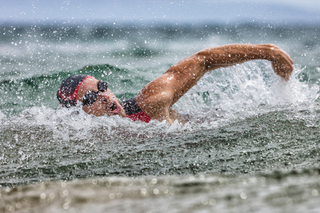 Photo pour Triathlon swim tired swimmer swimming in ocean in wave and rain storm . Professional male triathlon swimmer wearing cap, goggles and red triathlon tri suit training for ironman breathing out of water. - image libre de droit