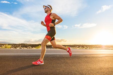 Photo pour Triathlon - Triathlete man running in triathlon suit training for ironman race. Male runner exercising on Big Island Hawaii. Sunset. - image libre de droit