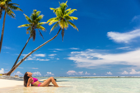 Photo for Beach vacation paradise suntan woman relaxing lying down sun tanning in tropical idyllic summer background in Caribbean with blue sky and palm trees. - Royalty Free Image