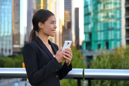 Photo pour Phone Asian business woman in suit outside texting on mobile smartphone. Happy smiling businesswoman realtor working using smart phone. Young multiracial chinese caucasian lady at work. - image libre de droit