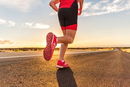 Foto de Running shoes on male triathlete runner - closeup of feet running on road. Man jogging outside exercising training for triathlon ironman outside at sunset. - Imagen libre de derechos
