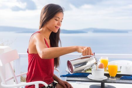 Photo for Coffee woman pouring tea in mug for breakfast at hotel room by Mediterranean sea on Europe vacation travel. Happy Asian girl enjoying morning brunch on couple honeymoon. - Royalty Free Image