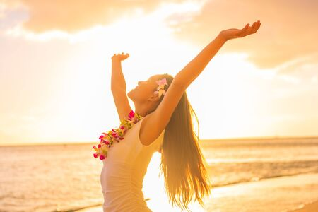 Photo pour Hawaii hula dancer woman wearing flower necklace lei on sunset beach dancing with open arms free in sunset relaxing on hawaiian travel vacation. Asian girl with fresh flowers hair, traditional dance. - image libre de droit