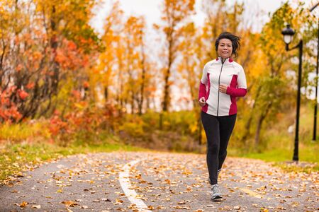 Photo pour Mature Asian woman running active in her 50s. Middle aged female jogging outdoor living healthy lifestyle in beautiful autumn city park in colorful fall foliage. Asian Chinese adult in her fifties. - image libre de droit