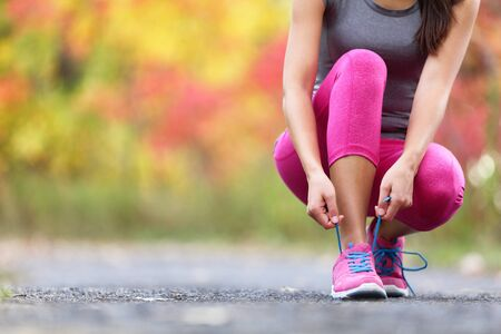Photo for Autumn running shoes girl tying laces ready to run in forest foliage background. Sport runner woman training cardio in outdoor fall nature in pink activewear leggings and footwear. - Royalty Free Image