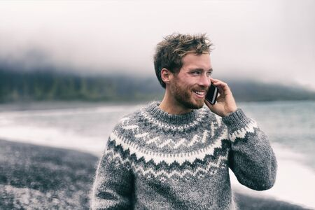 Photo pour Phone man talking on smartphone in winter sweater walking on black sand beach in Iceland. Icelandic wool clothes. Technology mobile cellphone. - image libre de droit