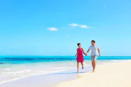 Photo pour Beach vacation honeymoon paradise travel destination - Young couple in love walking holding hands in idyllic holiday background. - image libre de droit