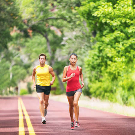Foto de Runners running on road outside two athletes training outdoor in summer nature jogging. Square crop. Woman and man run race. - Imagen libre de derechos