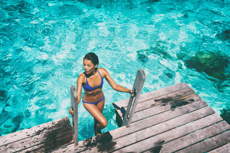Photo for Luxury resort bikini woman swimming coming out of water after swim on overwater bungalow terrace at high end hotel. Sexy Asian girl in swimwear with tanned body. - Royalty Free Image