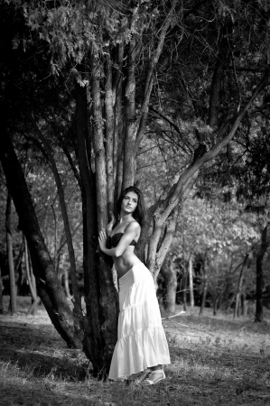 Beautiful brunette woman in black top and long white skirt standing near a cedar tree, dreaming and looking into the distance