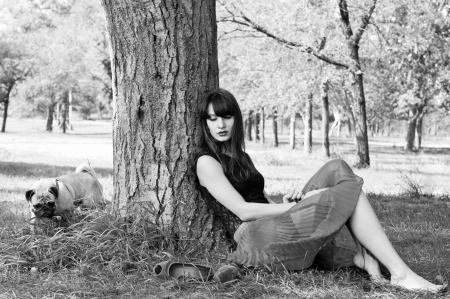 Black and white photography of beautiful barefooted brunette woman sitting near a tree with her shoes nearby and calling her pug dog pet