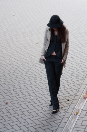Pretty brunette woman model wearing stylish black pants suit and gray rain coat, black hat with wide fields, high heels, red lips, hands in pockets, going down the street covered with pavement tiles  Copy space