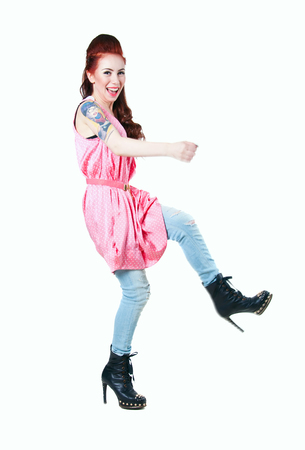 Studio portrait of pretty young woman model wearing pink dotted dress, ripped jeans, black boots with high heels and spikes, moving actively, dancing, smiling at camera, with high red hairstyle, big colorful tattoo on her right arm. Isolated on white