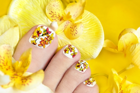 Pedicure with yellow orchids in the women s legs on a yellow background の写真素材