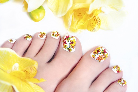 Flower pedicure with yellow orchids in the women s legs on a white background の写真素材