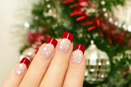 Winter manicure with red lacquer and white chips on the background of the Christmas tree の写真素材