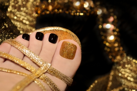 Luxury pedicure with black and gold lacquer on women s toes on the black and brilliant background