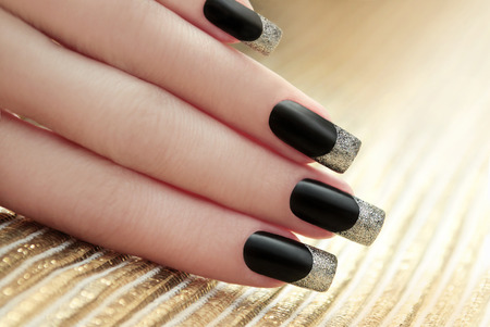 Black French manicure on Golden striped background.