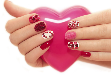 Manicure with rhinestones in the shape of hearts and pink balls on white and red nail Polish on a white background.