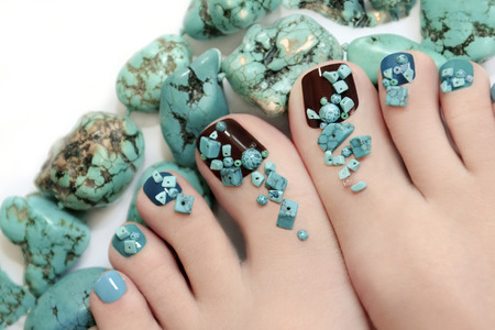 Pedicure with turquoise stones and jewelry made of turquoise on the women\\