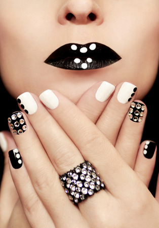 Multicolored manicure with white and black nail Polish decorated with rhinestones and a ring on his hand.