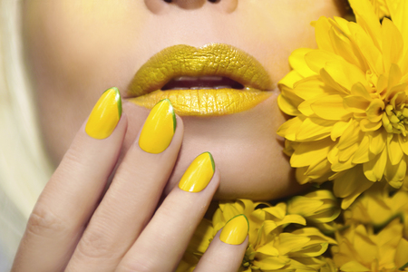 Photo pour Yellow makeup and manicure with a sharp oval shape of the nails on the woman with the flowers closeup. - image libre de droit