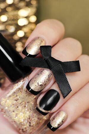 Foto de Black and gold French manicure with nail Polish in hand closeup. - Imagen libre de derechos