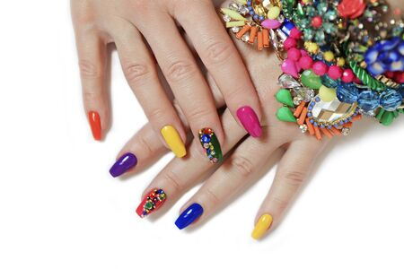 Foto de Creative bright saturated manicure on long nails with rhinestones. Nail art on women's hands on a white background with costume jewelry. - Imagen libre de derechos