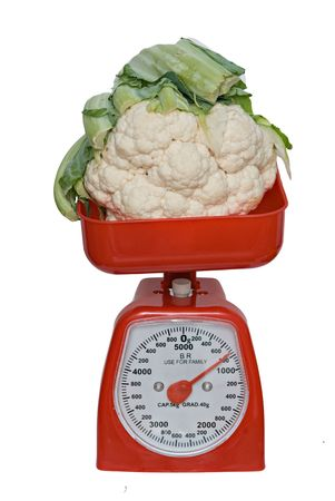 Kitchen scale weighting broccoflower isolated on white background