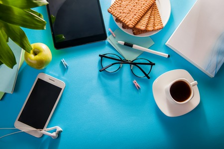 Workspace of a student on blue background. Studying with a cup of coffee and snacks, using a phone