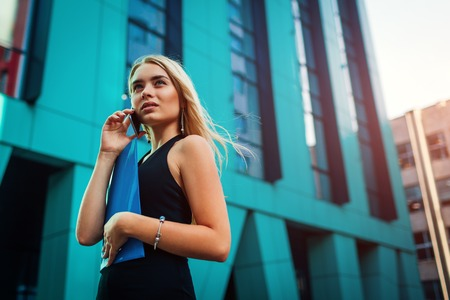 Young blonde businesswoman calling on smartphone and holding folder by business center in city. Communiation