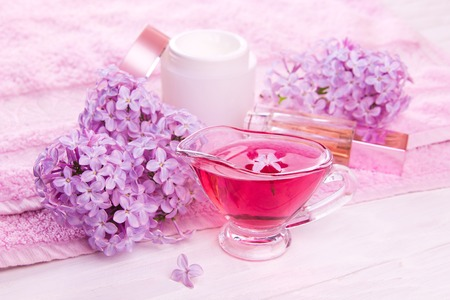 Spa essentials including with cream, pink towel, soap and oil with lilac. Natural cosmetics