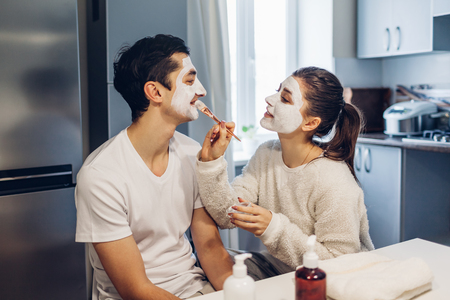 Foto de Woman applying clay mask on her boyfriends face. Young loving couple taking care of skin at home - Imagen libre de derechos