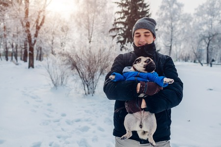 Pug dog walking on snow with his master. Puppy wearing winter coat. Man holding his pet in winter forest. Clothes for animals