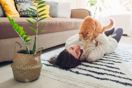 Photo pour Young woman playing with cat on carpet at home. Master lying on floor with her pet and holding kitten - image libre de droit