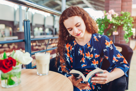 Photo pour Happy young woman reading book in shopping center while drinking coffee. Relaxing in cafe - image libre de droit