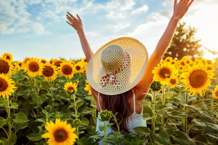 Photo for Happy young woman walking in blooming sunflower field raising hands and having fun. Summer vacation. - Royalty Free Image