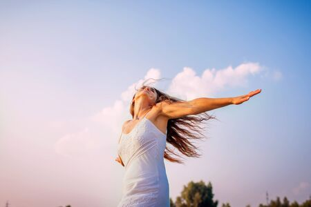 Photo for Young woman feeling free and happy raising arms and spinning around outdoors at sunset - Royalty Free Image