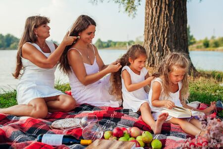 Photo pour Mother, grandmother and kids weaving braids to each other while the youngest reads book. Family having fun during picnic in park. Three denerations - image libre de droit