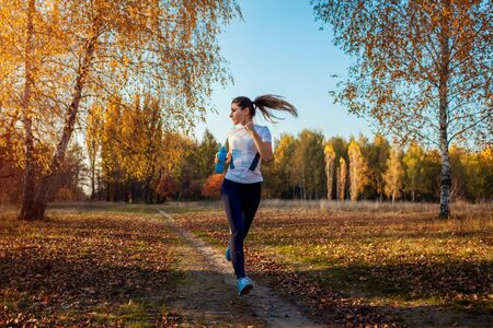 Foto de Runner training in autumn park. Woman running with water bottle at sunset. Active lifestyle. Workout - Imagen libre de derechos