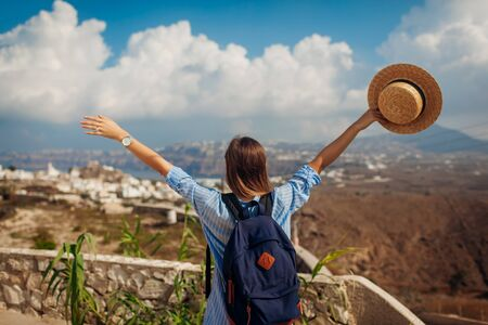 Photo pour Santorini traveler with backpack raised arms feeling happy looking at Akrotiri village, mountains landscape on island. Tourism, traveling during vacation - image libre de droit