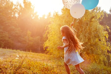 Photo pour Pretty little girl running with baloons in hand. Kid having fun in summer park. Outdoors activities - image libre de droit