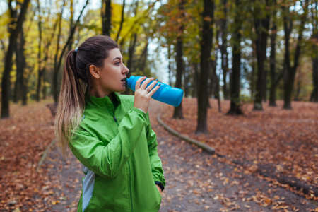 Photo for Runner having rest after workout in autumn park. Woman drinking water. Sportive active lifestyle - Royalty Free Image